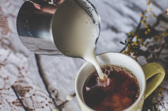 Imagem de xícara de chá preto e caneca com leite