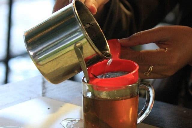 Imagem de chá sendo despejado em caneca
