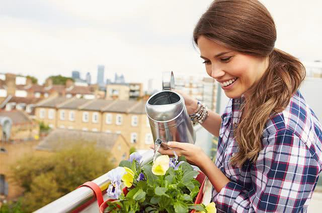 Imagem de mulher regando planta