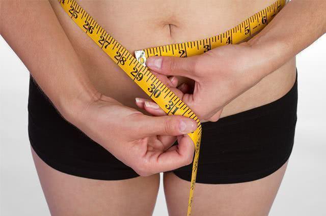 Mulher medindo a barriga