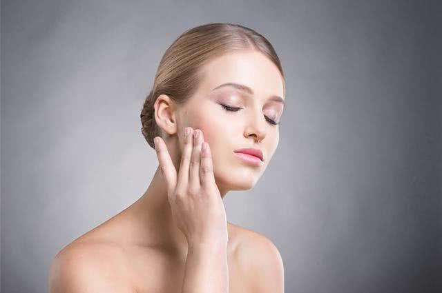Mujer frotando la mano sobre la piel de la cara