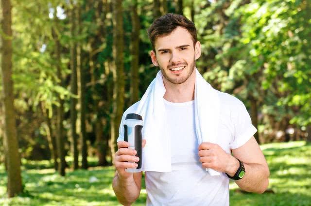 Imagem de homem jovem com toalha no pescoço segurando garrafa squeeze