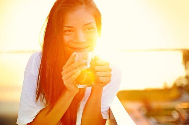 Imagem de mulher segurando caneca de chá no sol
