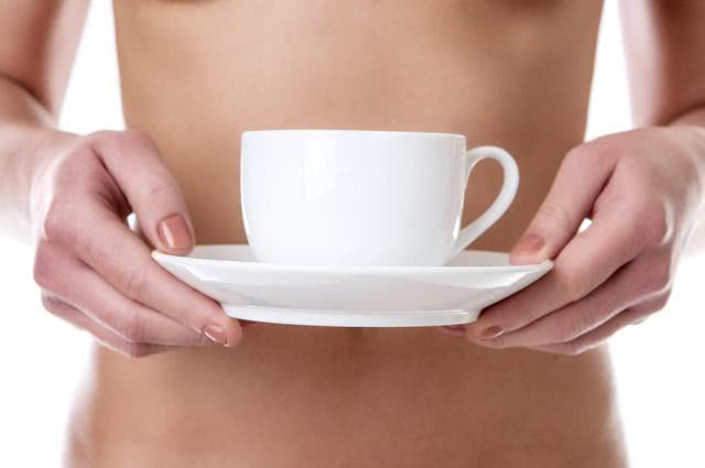 Imagem de mulher segurando xícara na altura da barriga