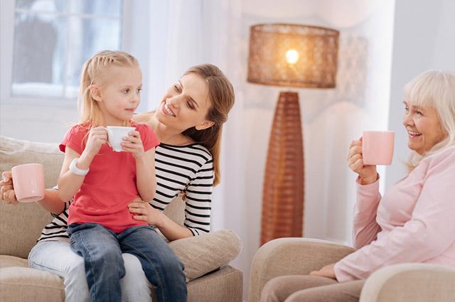 Duas mulheres e uma criança tomando chá