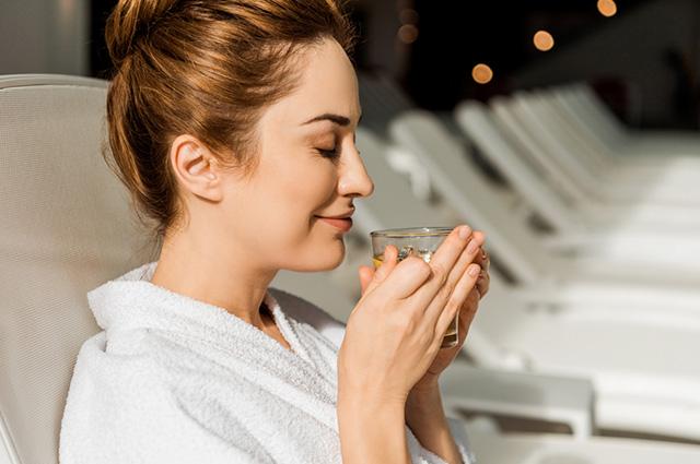 Mulher com os olhos fechados e cheirando um chá