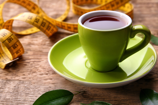 Xícara de chá preto com fita métrica
