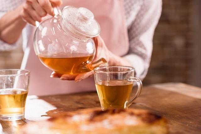 Mulher colocando chá na xícara